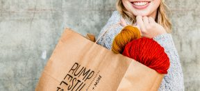 woman smiling and holding Rumpelstiltskin bag with yarn popping out.